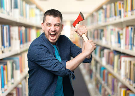 Young man wearing a blue outfit. Holding an axe. Stock Photo