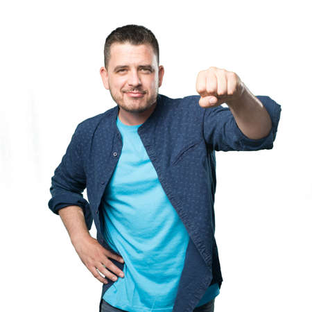 Young man wearing a blue outfit. Showing confident his fist. Stock Photo