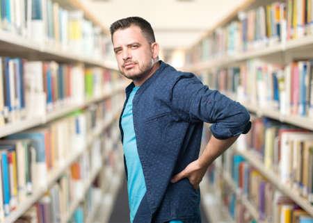 Young man wearing a blue outfit. Backache.