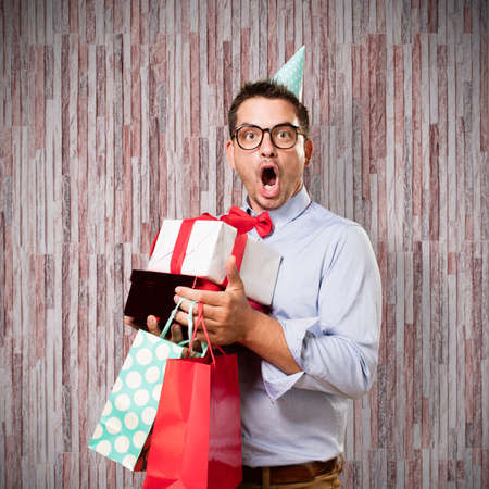 Man wearing a red bow tie and party hat. Holding gift. Looking surprised.