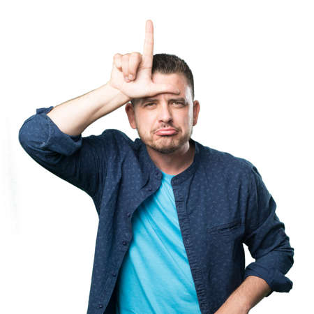 Young man wearing a blue outfit. Doing looser gesture.