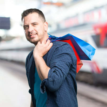 Young man wearing a blue outfit. Holding shopping bags. Stock Photo