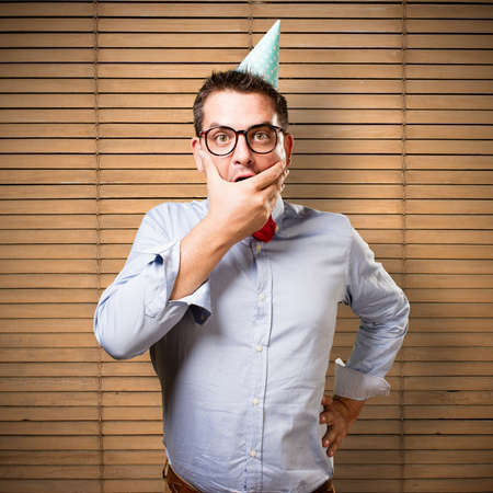 Man wearing a red bow tie and party hat. Looking surprised. Stock Photo