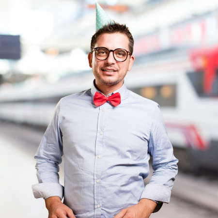 Man wearing a red bow tie and party hat. Looking bliss.