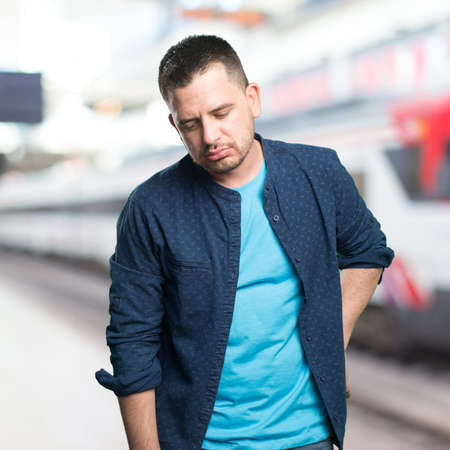 Young man wearing a blue outfit. Looking tired.