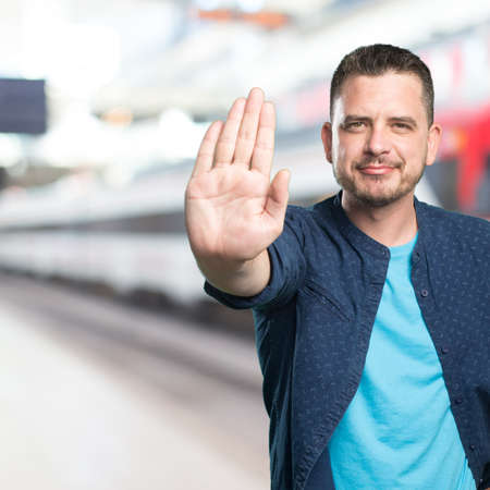Young man wearing a blue outfit. Doing stop gesture. Stock Photo