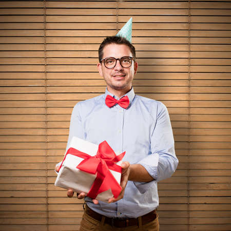 Man wearing a red bow tie and party hat. Holding gift.