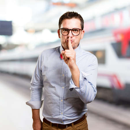 Man wearing a red bow tie. Doing silence gesture.