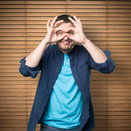 Young man wearing a blue outfit. Doing glasses gesture. Stock Photo