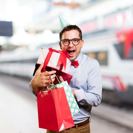 Man wearing a red bow tie and party hat. Holding gift. Looking happy.