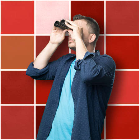 Young man wearing a blue outfit. He is using binocular Stock Photo