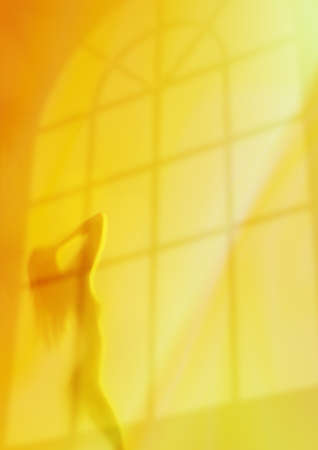 myst: Silhouette of young woman gazing to the light beams on a yellow background