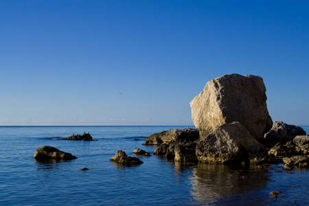Seaside with rocks and birds in warm, clear weather Stock Photo - 3909191