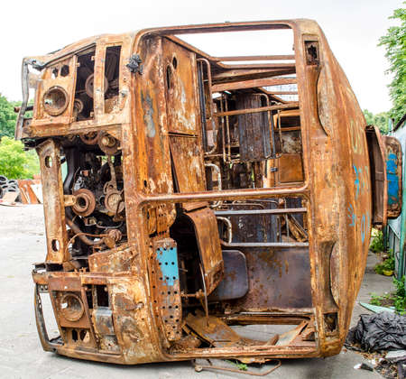junked: Old rusty bus partially collapsed in the backyard Stock Photo