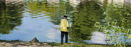 clr: The fisherman stay a back on the bank of river with fishing tackles