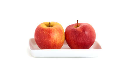 ripe apples on the white plate on white background Stock Photo