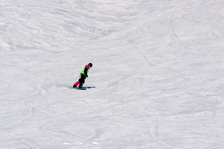 girl in a colorful suit is on a snowboard rides with mountains Reklamní fotografie