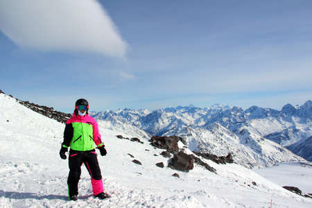 girl in a colorful suit stands on top of a snowy mountain