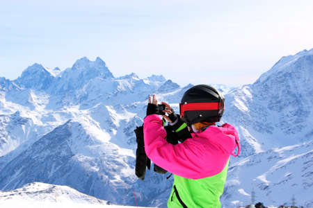 girl in a colorful suit photographed on top of a snowy mountain Reklamní fotografie