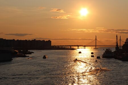 orange sunset over the river with a big bridge and boats