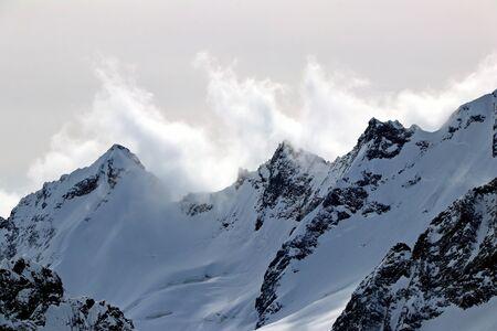 Snowy Mountains peaks in the clouds blue sky Caucasus Standard-Bild
