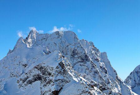 Panoramablick auf die schneebedeckten Berggipfel im blauen Himmel der Wolken Kaukasus Standard-Bild