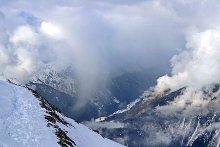 Picos de las montañas nevadas en el cielo azul de nubes