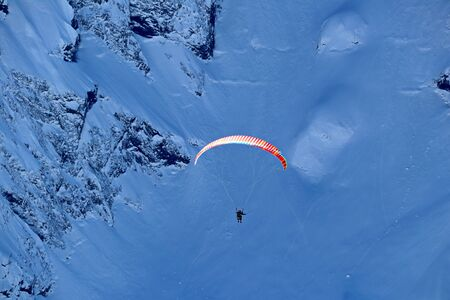 paraplane flying over snowy Caucasus mountains and sunny blue sky Stock Photo