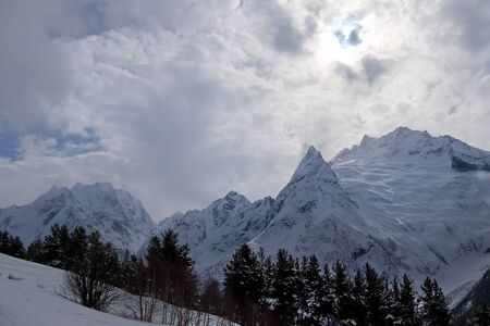 Snowy Mountains peaks in the clouds blue sky