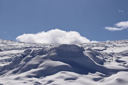 snowy mountain side and cloud in the blue sky