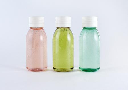 Tres botellas de plástico con líquidos de colores sobre fondo blanco Foto de archivo