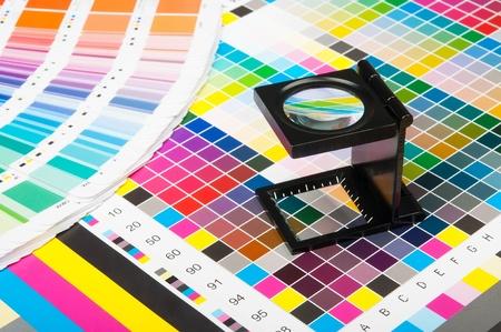 La lente d'ingrandimento in piedi su una foglia di prova di stampa