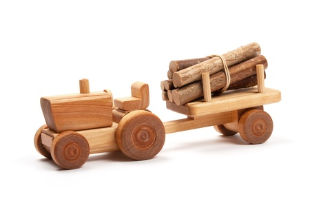 Wooden toy tractor with trailer on white