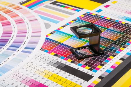 La lente d'ingrandimento in piedi su una foglia di prova di stampa Archivio Fotografico - 27577434