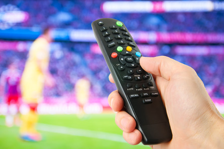 Hand hold remote control in front of tv photo