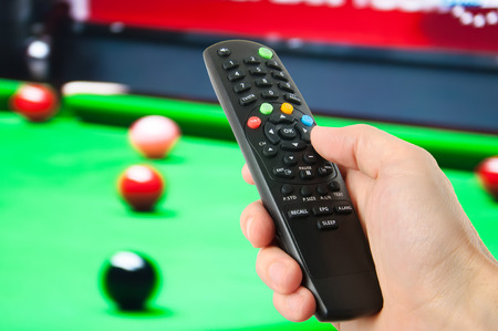 Hand holding remote control in front of tv Stok Fotoğraf
