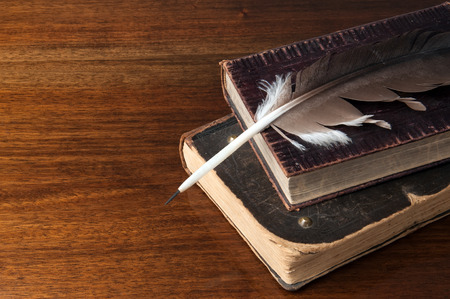 Old books and a fountain pen on wooden table background