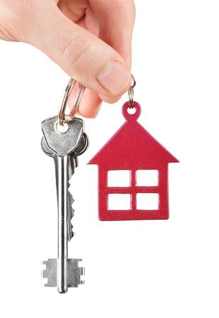 白い背景で隔離の手で家の鍵