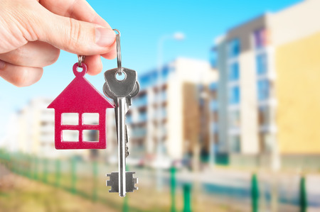 housing estate: Handing keys in the house background Stock Photo