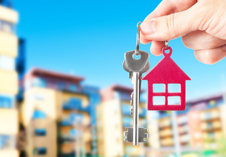 tenement: Handing keys in the house background Stock Photo