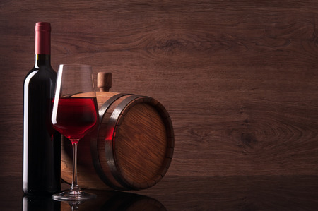 Bottle of red wine, glass and barrel on wooden background