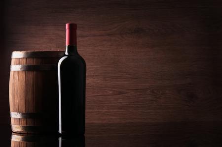 Bottle of red wine and barrel on dark background