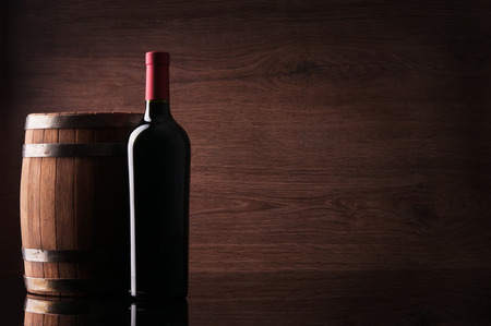 Bottle of red wine and barrel on dark background