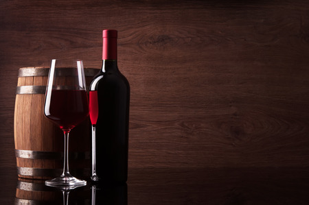 expensive food: Bottle of red wine, glass and barrel on dark wooden background Stock Photo