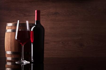 Bottle of red wine, glass and barrel on dark wooden background Standard-Bild