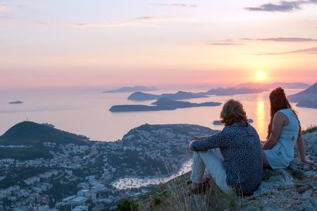 美しい夕日を背景に若い男女