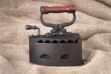 The old coal iron on a fabric background Standard-Bild