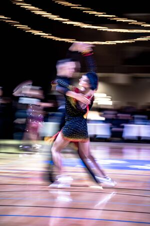 Blurred dancing couple in ballroom