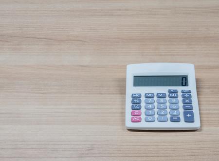 reckon: white calculator on the wooden desk