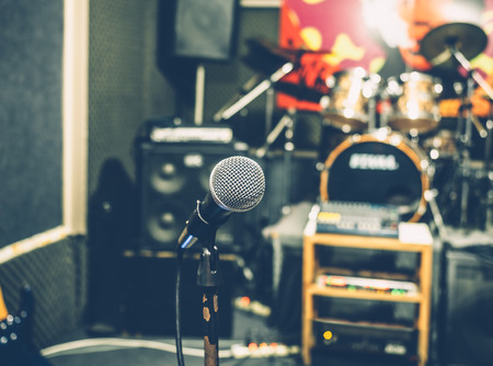 concert hall: Selective focus on microphone with blurry music studio background, vintage style
